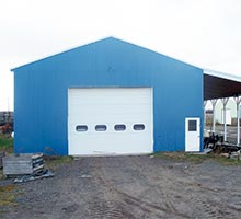 Large steel pole barn receives some color while making it look new again.