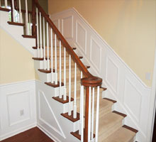 Base of stairs at the foyer with new paint on walls, moldings, riser and balusters.